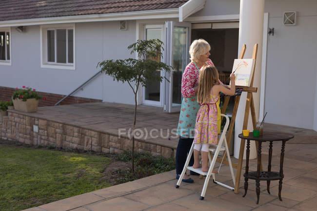 Nipote e nonna pittura su tela nel portico — Foto stock