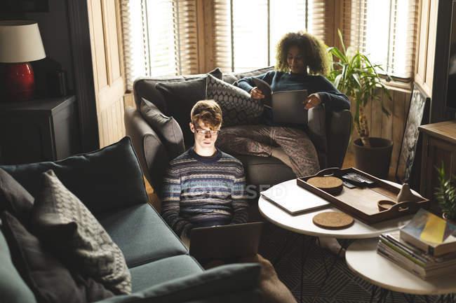 Coppia che utilizza laptop e libro di lettura in soggiorno a casa — Foto stock