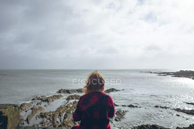 Vista posteriore della donna rossa che si rilassa in spiaggia . — Foto stock