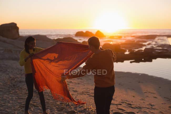 Casal se divertindo com cobertor na praia durante o pôr do sol — Fotografia de Stock