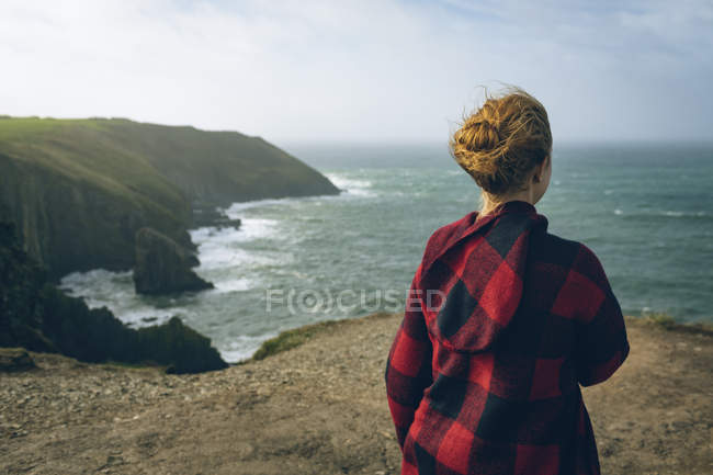 Vista posteriore della donna rossa in piedi in spiaggia panoramica . — Foto stock