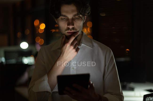 Ejecutivo masculino usando tableta digital en la oficina por la noche - foto de stock