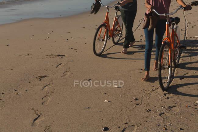 Section basse de couple avec vélos marchant sur la plage — Photo de stock