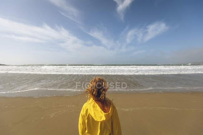 Visão traseira da mulher ruiva em casaco amarelo em pé na praia . — Fotografia de Stock