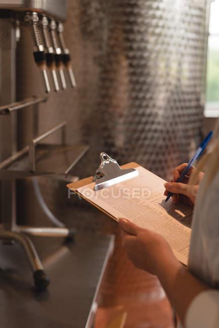 Media sección de trabajadora, escribir en el portapapeles en fábrica - foto de stock