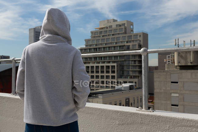Rear view of casual woman in grey hoodie posing in terrace — Stock Photo