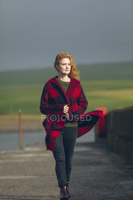 Femme rousse bien pensés qui marche en Côte venteuse. — Photo de stock