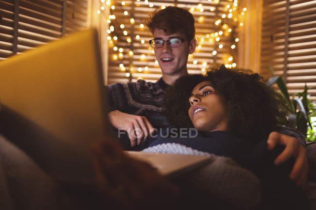Couple en utilisant un ordinateur portable dans le salon confortable à la maison — Photo de stock