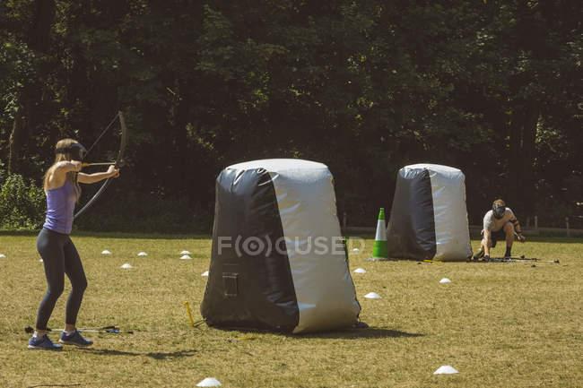Мужчина и женщина практикуют стрельбу из лука в учебном лагере на солнце — стоковое фото