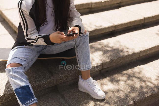 Bassa sezione di skateboarder femminile utilizzando il telefono cellulare in città — Foto stock