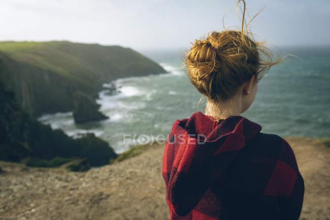 Vista posteriore della donna rossa in piedi in spiaggia . — Foto stock