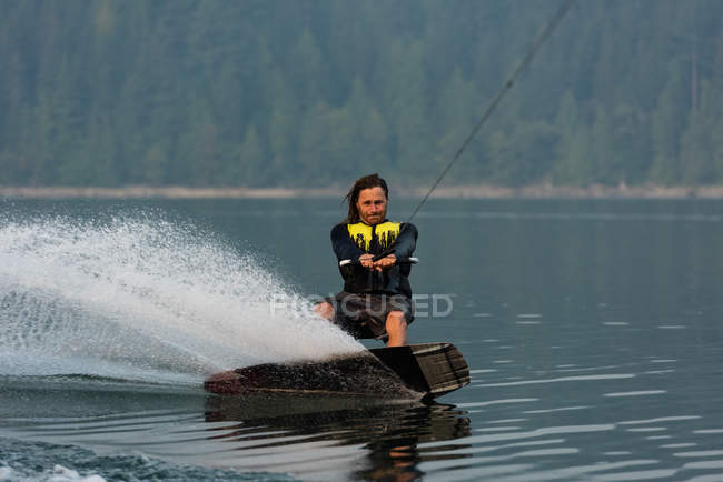 Extreme male athlete wakeboarding in river water — Stock Photo