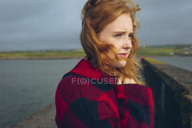 Продуманий руда жінку, що стояли в пляж. — стокове фото