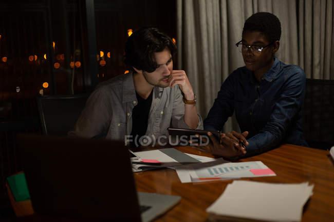 Керівники обговорювати над цифровий планшетний в офісі вночі — стокове фото