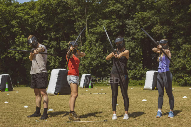 Group of people training archery at boot camp in sunlight — Stock Photo