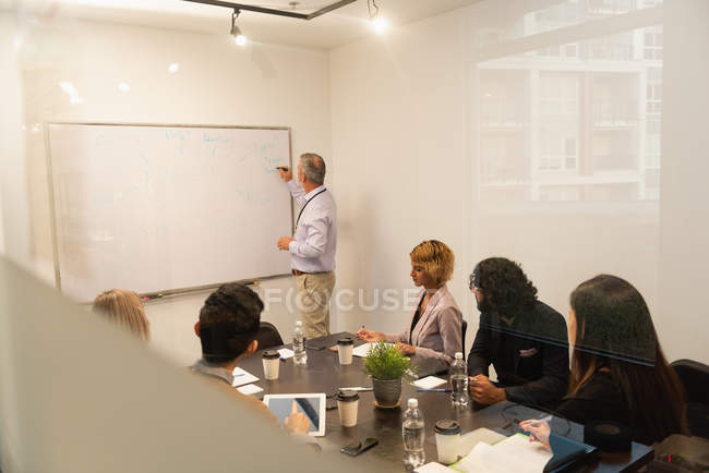 Executives discussing over whiteboard in conference room at office — Stock Photo