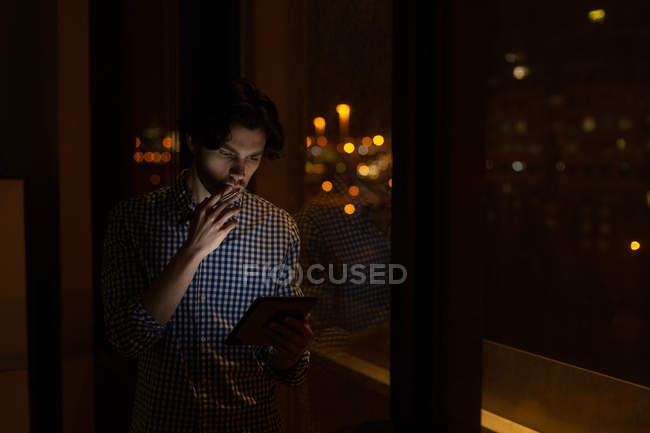 Männliche Führungskraft nutzt nachts digitales Tablet im Büro — Stockfoto