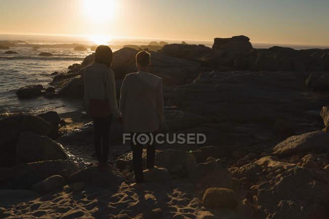 Vista posteriore della coppia che si tiene per mano mentre cammina sulla spiaggia — Foto stock