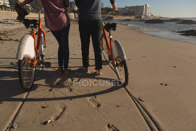 Low section of couple with bicycles walking on beach — Stock Photo