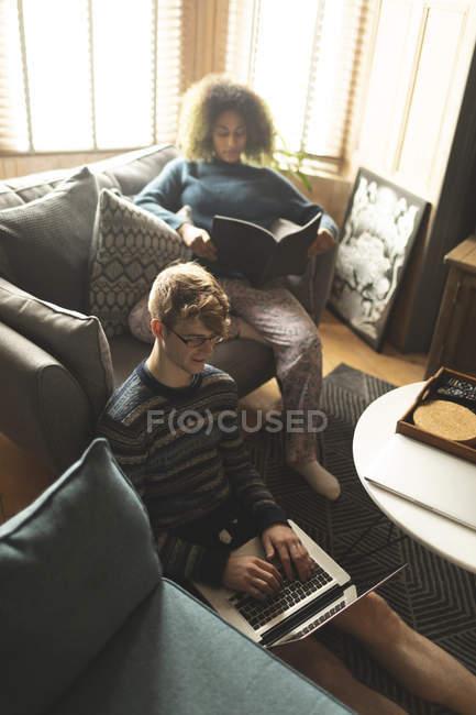 Пара с ноутбуком и книгой для чтения в гостиной дома — стоковое фото