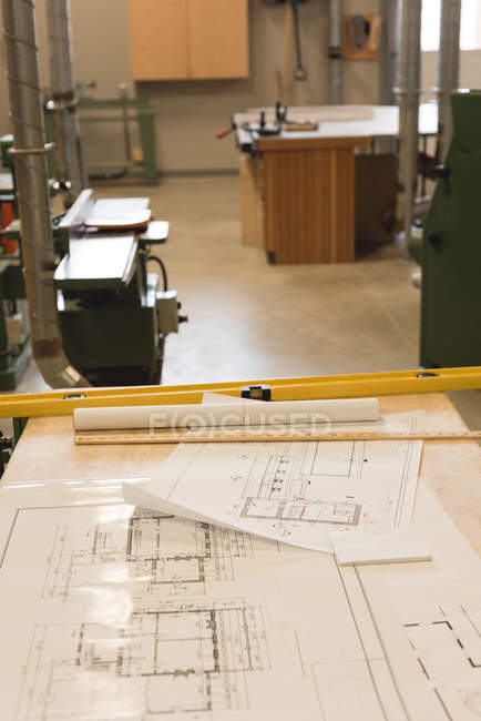 Blueprints and measuring instrument on table in workshop — Stock Photo
