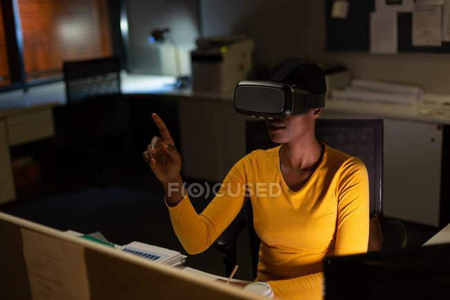 Жіночий виконавчий за допомогою віртуальної реальності гарнітуру в офісі вночі — стокове фото