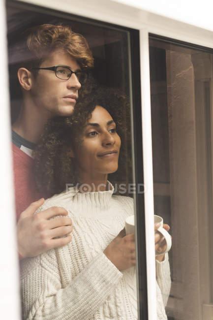 Coppia premurosa guardando attraverso la finestra a casa — Foto stock