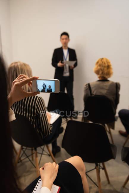 Executive scattare foto con il telefono cellulare in ufficio — Foto stock
