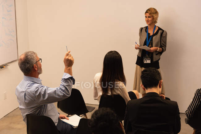 Executive raising hand during meeting in office — Stock Photo
