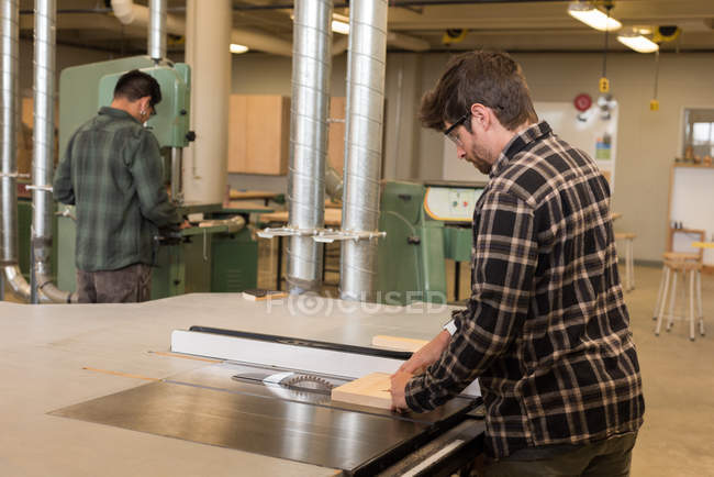 Attentive craftsmen working in industrial workshop — Stock Photo