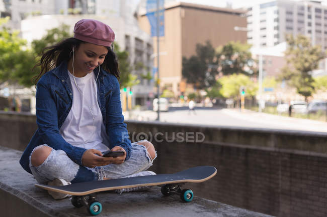 Smiling female skateboarder listening music on mobile phone — Stock Photo