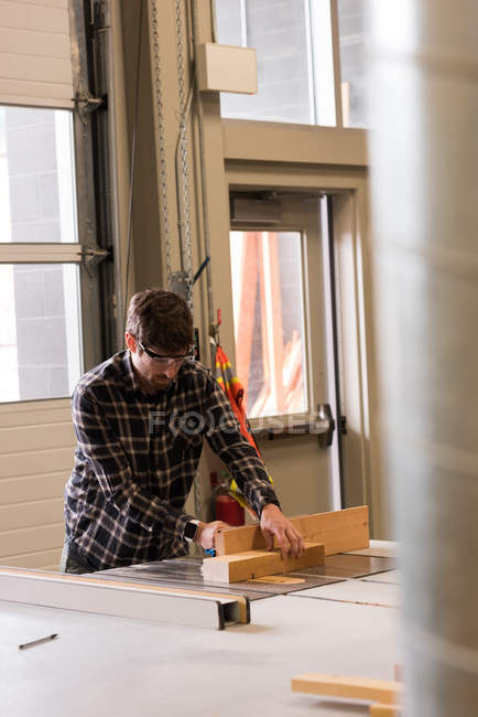 Attentive craftsman working with wood in workshop — Stock Photo