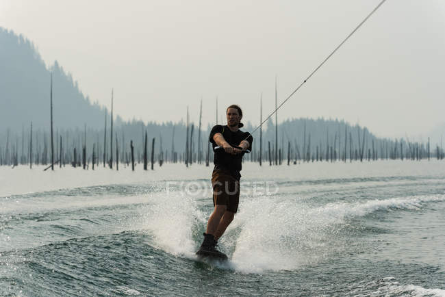 Young man splashing water while wakeboarding in river — Stock Photo
