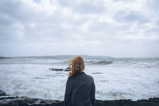 Rear view of redhead woman standing in beach overlooking ocean. — Stock Photo