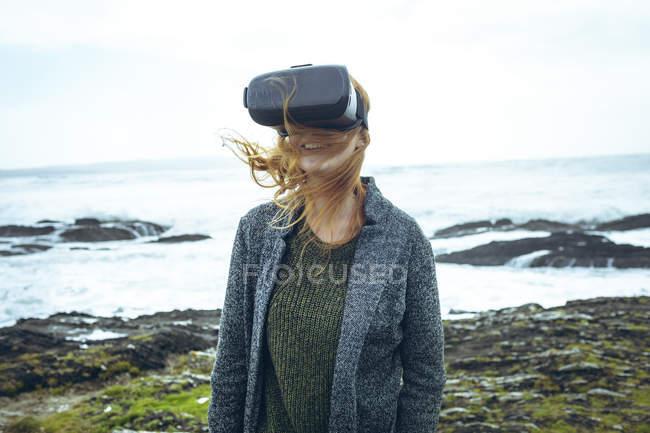 Руда жінці за допомогою віртуальної реальності гарнітуру на пляжі. — стокове фото