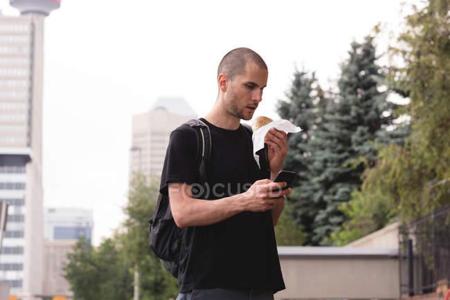 Joven usando teléfono móvil teniendo burger - foto de stock