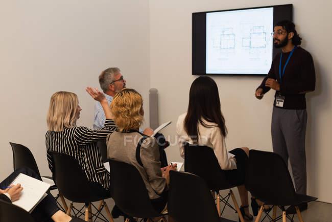Exekutive, die Hand heben, während der Sitzung im Büro — Stockfoto