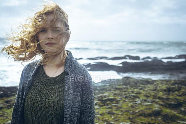 Portrait de femme rousse, debout dans la plage de vent. — Photo de stock