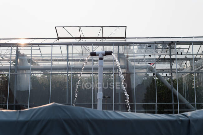 Water flowing from pipes of greenhouse in farm — Stock Photo