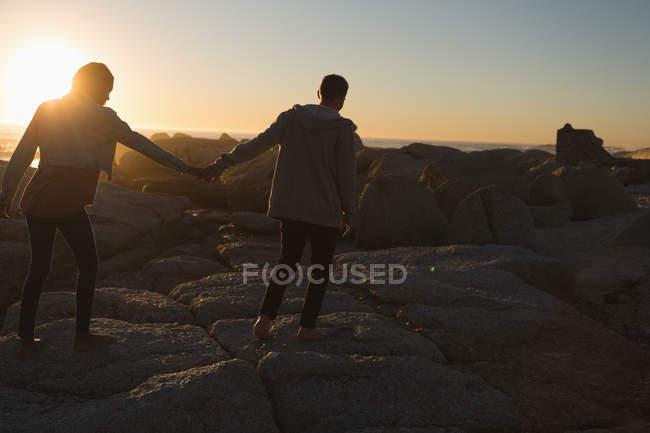 Vista trasera de la pareja cogida de la mano mientras camina por la playa - foto de stock