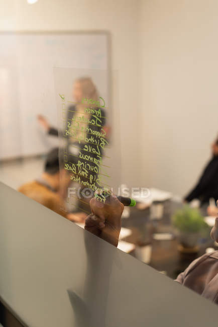 Close-up of female executive writing on glass wall in office — Stock Photo