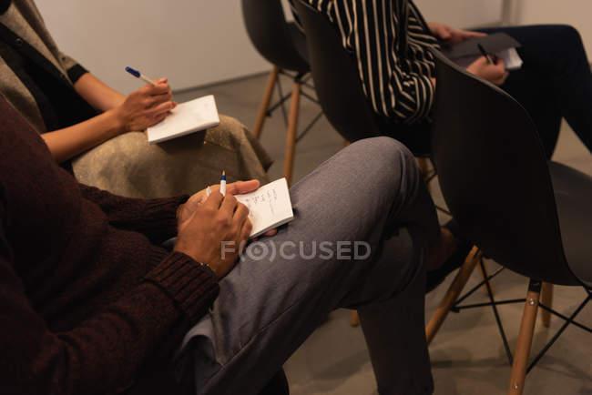 Средняя секция руководителей, пишущих на блокноте в офисе — стоковое фото