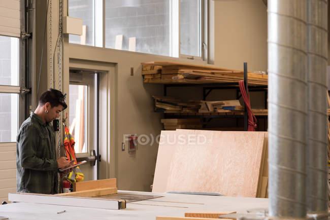 Side view of craftsman using digital tablet in workshop — Stock Photo