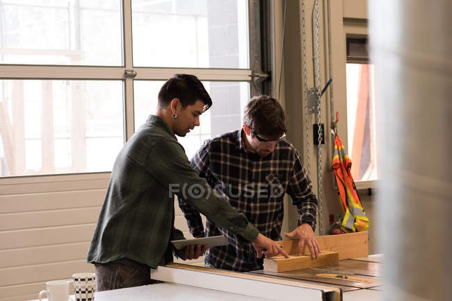 Deux artisans discutant sur planche de bois en atelier — Photo de stock