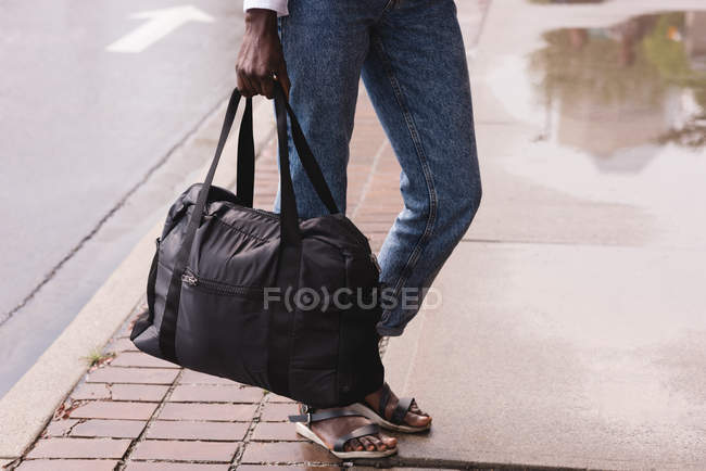 Close-up of woman with handbag standing on sidewalk — Stock Photo