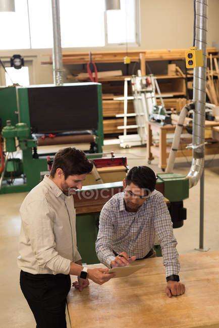 Deux artisans discutant sur tablette numérique en atelier — Photo de stock