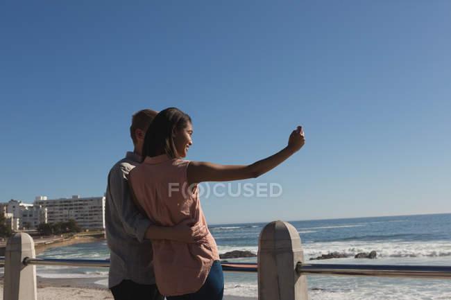 Романтична пара беручи selfie на набережній біля пляжу — стокове фото