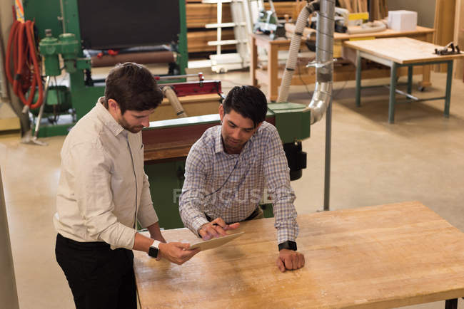 Two craftsmen discussing over digital tablet in workshop — Stock Photo