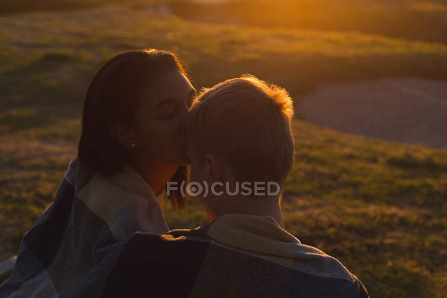 Couple kissing on beach during sunset — Stock Photo