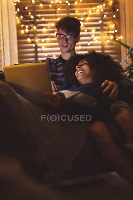 Couple utilisant un ordinateur portable dans le salon avec des lumières de fées à la maison — Photo de stock